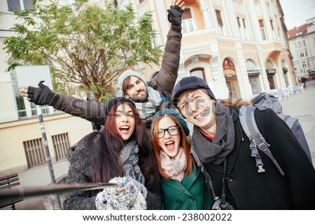 Group Of Cheerful Tourists Taking Selfie With The Help Of Monopod - stock photo