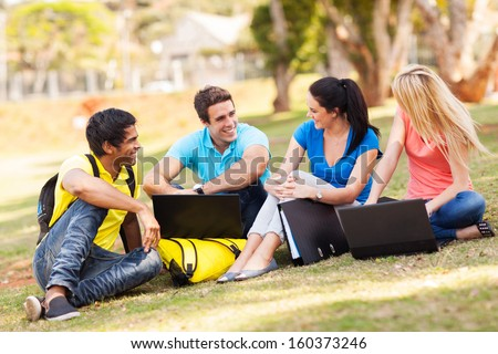 group of cheerful university students relaxing outdoors on campus - stock photo