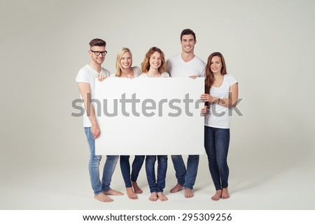 Group of Cheerful Young Friends Showing Large White Board with Copy Space Against Off-White Background Inside the Studio. - stock photo