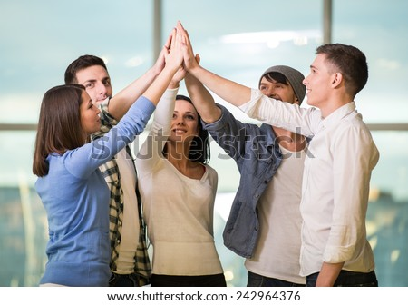 Group of cheerful young people are standing close to each other and holding hands up.