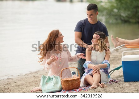 Group of cheerful young people having fun on the beach - stock photo