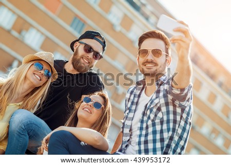 Group of cheerful young people taking selfie in the city - stock photo