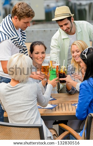 Group of cheerful young people toasting with cocktails outdoor terrace - stock photo