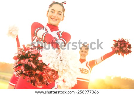 Group of cheerleaders performing outdoors  - Concept of cheerleading team sport training at high school during sunset - Tilted horizon composition and warm filter with sun backlighting - stock photo