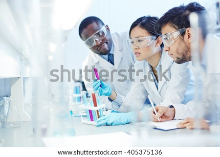 Group of chemists looking at tubing - stock photo