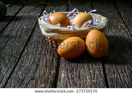 Group of chicken eggs on old wooden table with shadow - stock photo