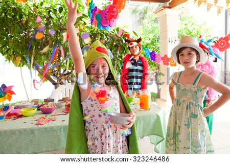 Group of children dressing up in fancy dresses at a colorful birthday party in a home garden with decorations and confetti, food and joyful expressions, outdoors lifestyle. Kids activities and fun. - stock photo