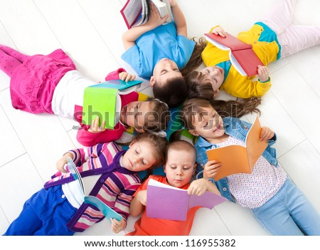 Group of children enjoying reading together - stock photo
