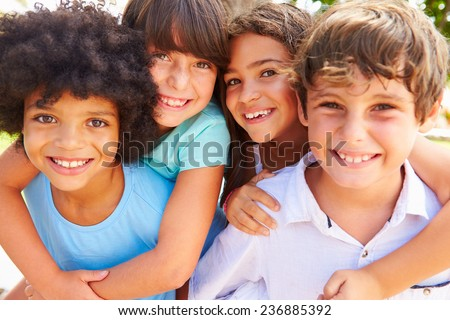 Group Of Children Giving Each Other Piggyback Rides