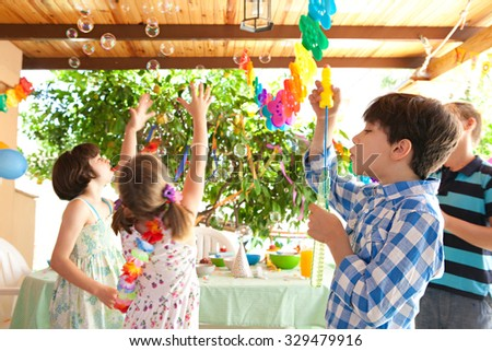 Group of children having fun at a birthday party in a home garden blowing and catching bubbles joyfully, house exterior. Kids playing at party, outdoors. Fun and activities on holiday, sunny day. - stock photo