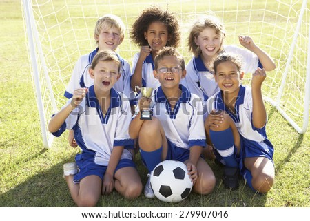 Group Of Children In Soccer Team Celebrating With Trophy - stock photo