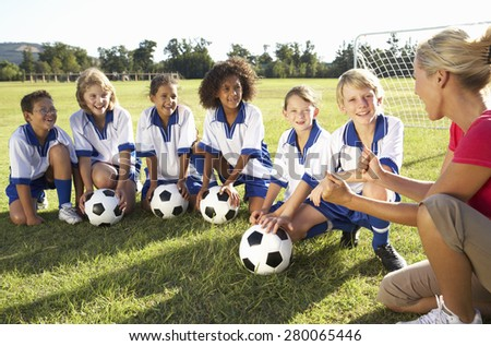 Group Of Children In Soccer Team Having Training With Female Coach - stock photo