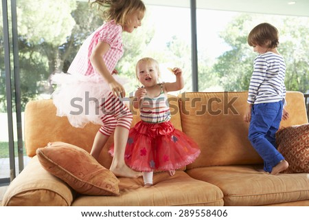 Group Of Children Jumping On Sofa - stock photo