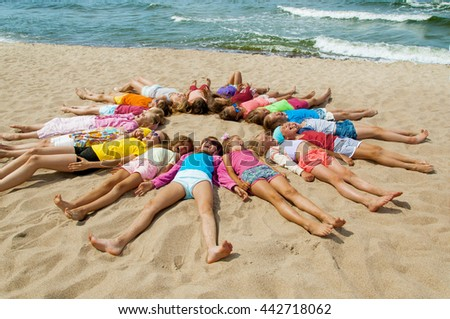 Group of children laying on the beach - stock photo