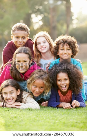 Group Of Children Lying On Grass Together In Park - stock photo