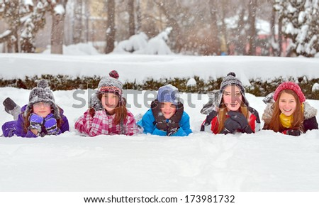 Group of children playing on snow in winter time - stock photo