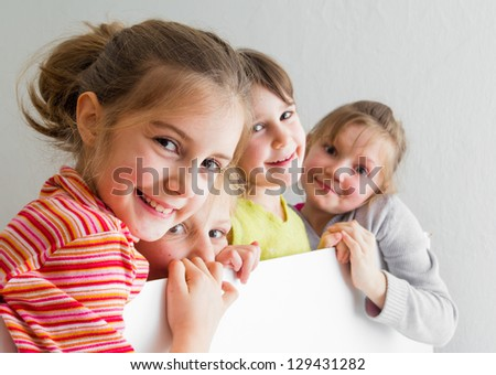 Group of children posing and hiding behind a large white table - stock photo