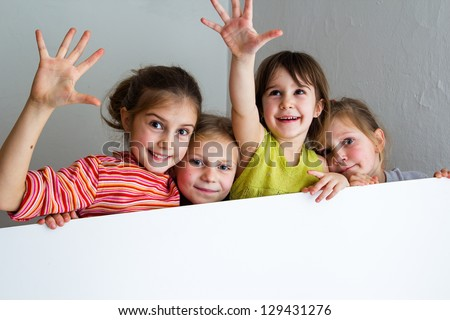 Group of children posing and hiding behind a large white table -copy-space - stock photo