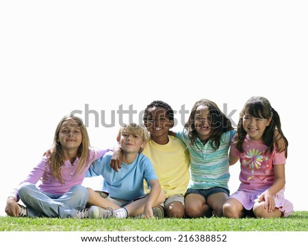 Group of children sitting on grass, smiling, portrait, cut out - stock photo