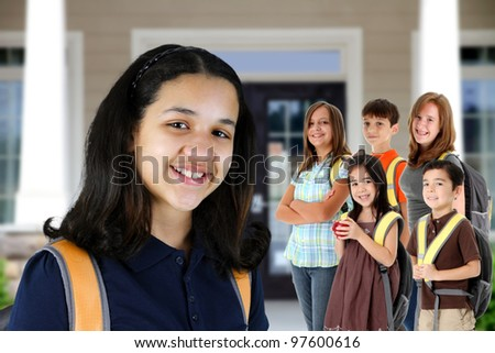 Group of children standing in front of their school - stock photo