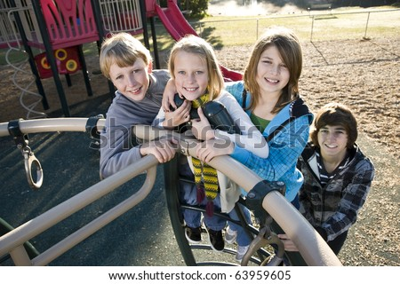 Group of children (10 to 15 years) standing together on playground equipment - stock photo
