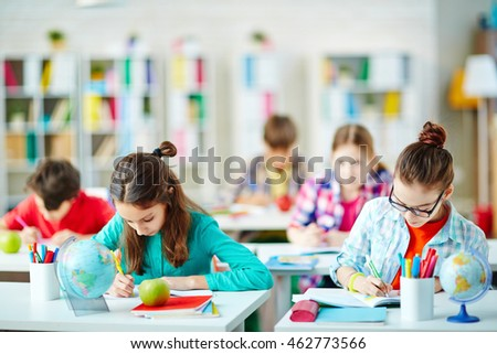 Group of children writing at their desks at classroom