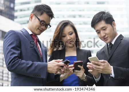 Group of Chinese business colleagues using mobile phone's outside the office. - stock photo