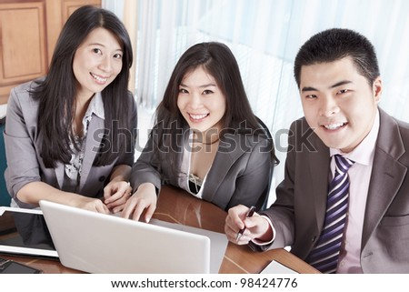Group of Chinese business people smiling to camera in the office - stock photo