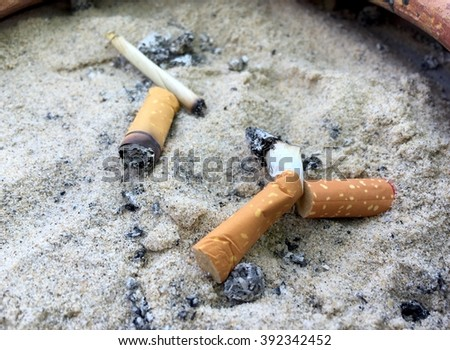 Group of cigarette in ashtray with sand, quitting smoking conceptual. Cigarette butts. - stock photo