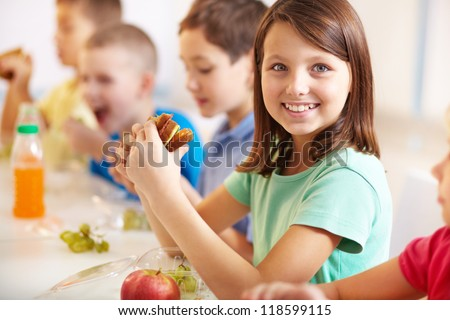 Group of classmates having lunch during break with focus on smiling girl with sandwich