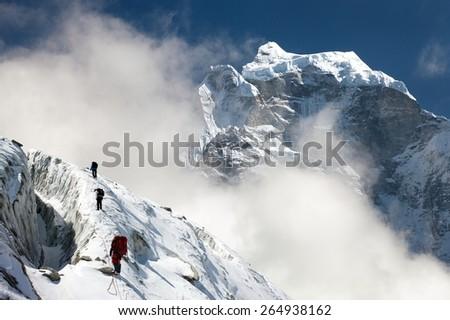 group of climbers on mountains montage to mounts Kangtega and Thamserku, Everest area, Khumbu valley, Nepal - stock photo