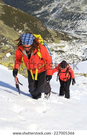 Group of climbers on steep snow covered face of the mountain - stock photo