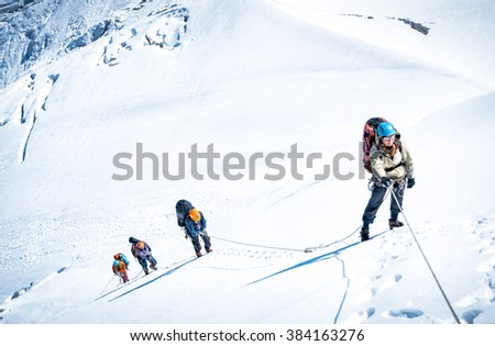 Group of climbers reaching the summit.  - stock photo