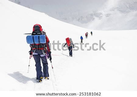 Group of climbers reaching the summit of mountain - stock photo