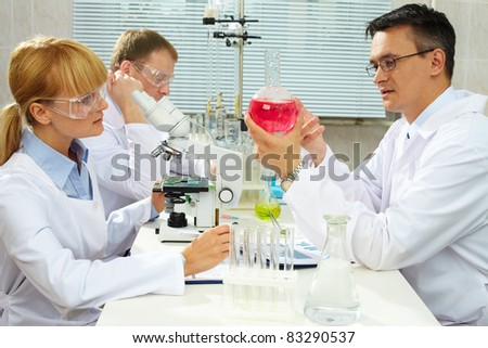 Group of clinicians studying new substance in laboratory - stock photo
