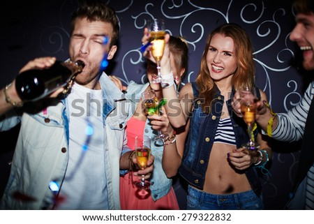 Group of clubbing friends with champagne having fun at party - stock photo