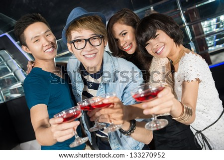 Group of clubbing young people clinking glasses of cocktail