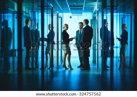 Group of colleagues consulting in corridor of business center - stock photo