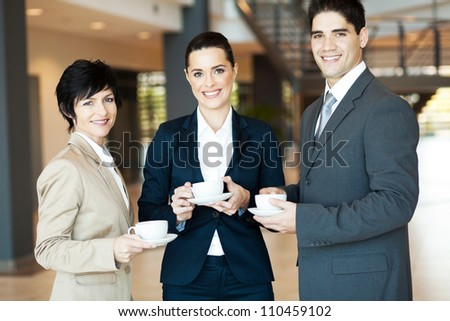 group of colleagues having coffee break at work - stock photo