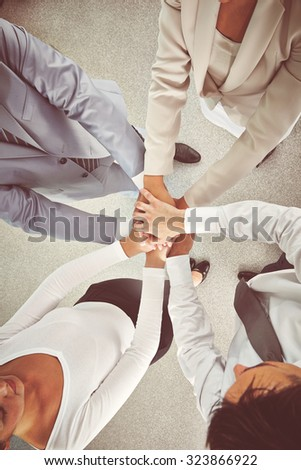 Group of colleagues making pile of hands - stock photo
