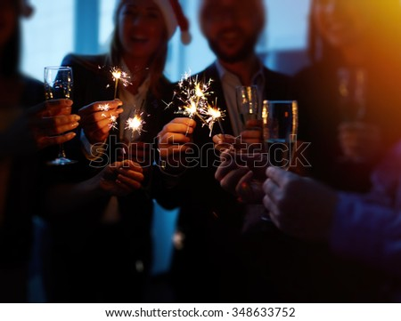 Group of colleagues with flutes holding Bengal lights - stock photo