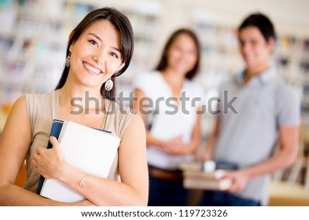 Group of college students at the library smiling - stock photo