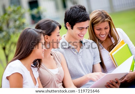 Group of college students exchanging notes outdoors - stock photo