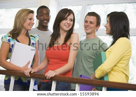 Group of college students leaning on banister - stock photo