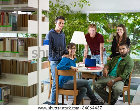 group of college students looking at camera in library. Horizontal shape, front view, full length - stock photo