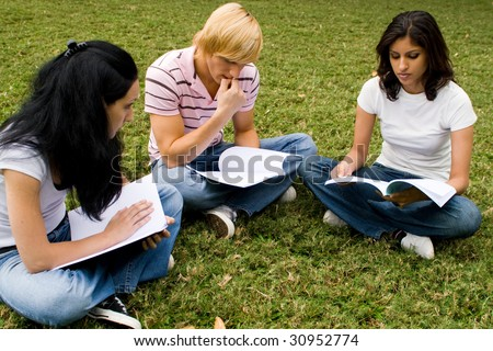 group of college students sitting in circle and reading book in the park - stock photo