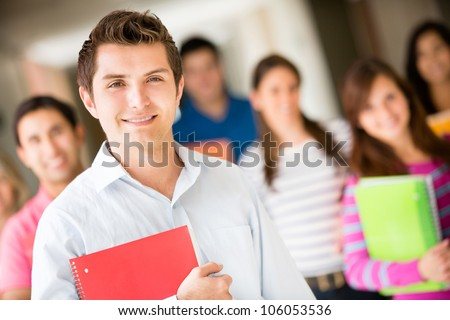Group of college students smiling and holding notebooks - stock photo