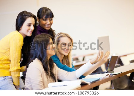 group of college students using tablet computer in classroom - stock photo