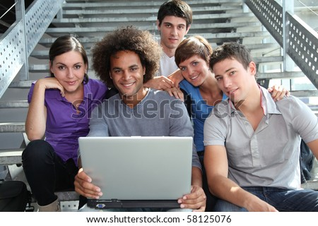 Group of college students with laptop computer - stock photo