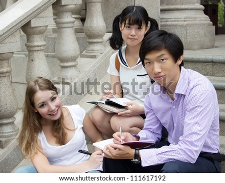 Group of college students writing in books. Students study outside of school campus. Friends working together on homework - stock photo